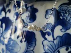 So dainty this little necklace is made of sterling silver rose and chain two swarovski pearls along side of rose to see go ~ https://www.etsy.com/listing/219438839/hand-wired-sterling-silver-rose-necklace