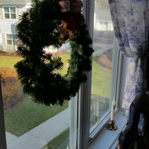 One small wreath hangs in the center window - Also 3 lights on the window sill ~